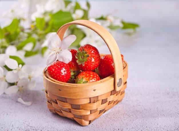 Frische reife erdbeeren in einem kleinen korb.