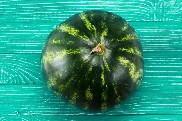 Frische reife ganze wassermelone auf grünem hintergrund