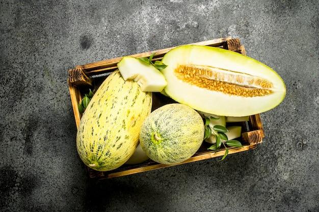 Frische reife geschnittene melone auf einem rustikalen hintergrund