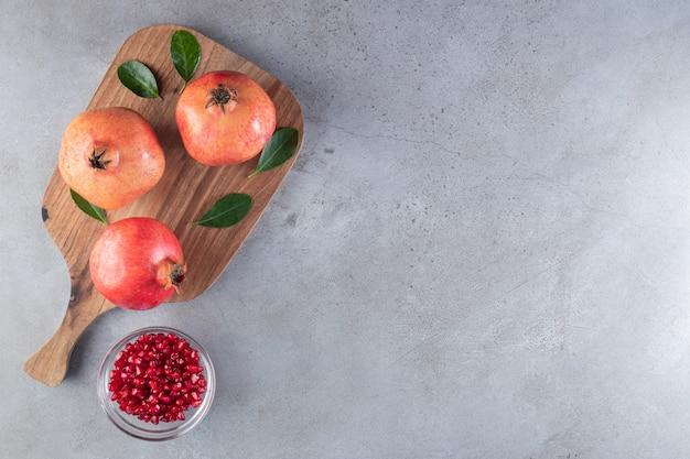 Frische reife granatäpfel mit grünen blättern auf holzschneidebrett.