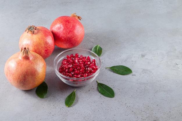 Frische reife granatäpfel mit samen auf steinhintergrund gelegt.