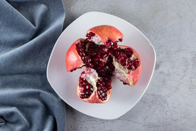 Frische reife granatäpfel mit samen auf weißen teller gelegt.