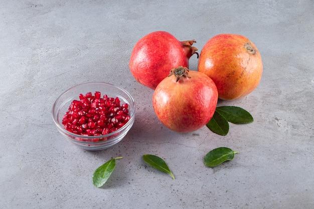 Frische reife granatäpfel mit schüssel samen auf steintisch gelegt.
