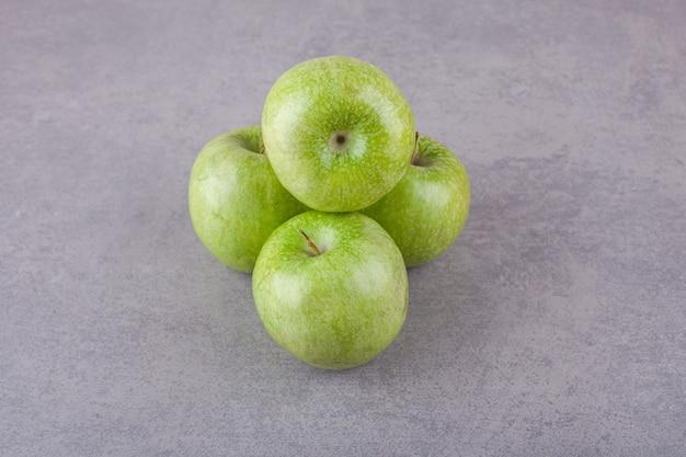 Frische reife grüne äpfel auf eine steinoberfläche gelegt.