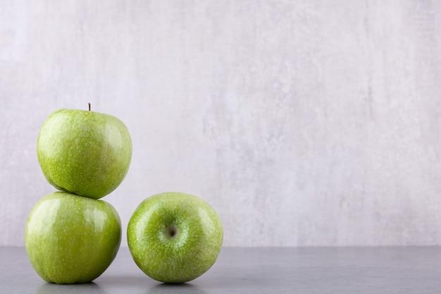Frische reife grüne äpfel auf steinhintergrund gelegt.