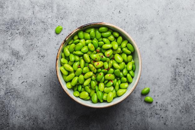 Frische reife grüne edamame-bohnen ohne schoten in schüssel auf grauem steinhintergrund. ansicht von oben, nahaufnahme. leichter und gesunder asiatischer snack gute quelle für vegetarisches protein für diät und ernährung