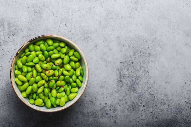 Frische reife grüne edamame-bohnen ohne schoten in schüssel auf grauem steinhintergrund mit platz für text. ansicht von oben, nahaufnahme. leichter und gesunder asiatischer snack gute proteinquelle für diät und ernährung