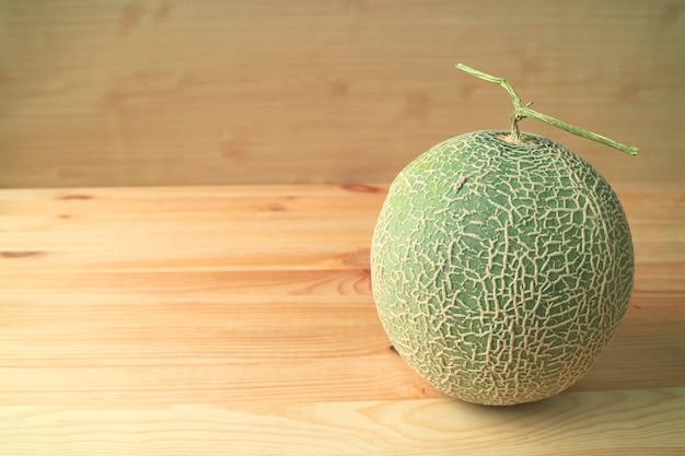Frische reife kantalupen-melone oder ganze muskmelon-frucht mit dem stamm lokalisiert auf holztisch