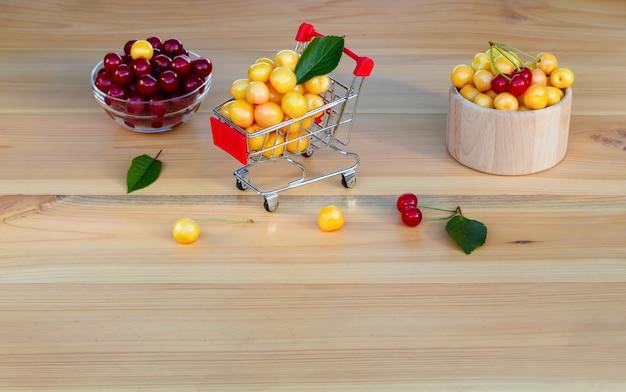 Frische reife kirschen im einkaufswagen, konzept des kaufens von früchten und beeren.