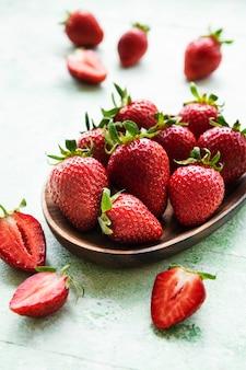 Frische reife köstliche erdbeeren in einer holzschale auf grünem holzhintergrund