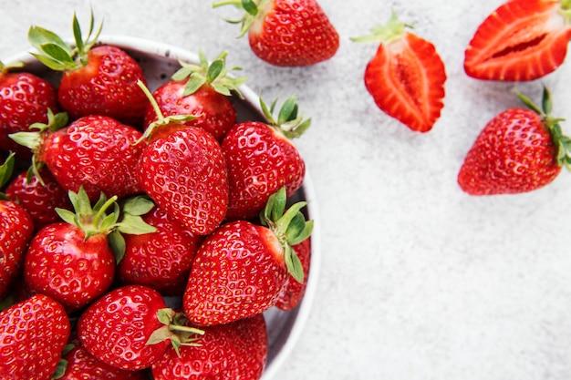 Frische reife köstliche erdbeeren in einer weißen schüssel auf einem grauen steinhintergrund