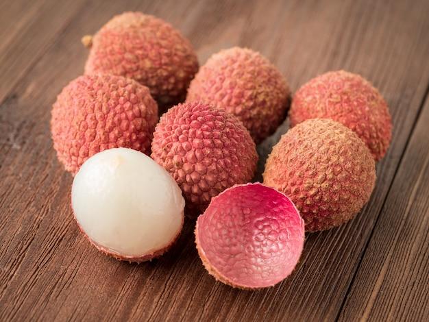 Frische reife litschifrucht auf einem holztisch, makro, seitenansicht.