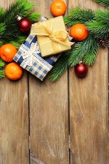 Frische reife mandarinen, weihnachtsschmuck und tannenbaumknospe auf holzuntergrund