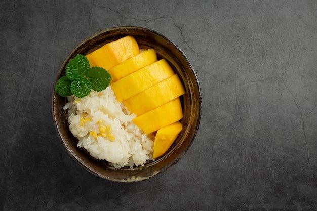 Frische reife mango und klebreis mit kokosmilch auf dunkler oberfläche