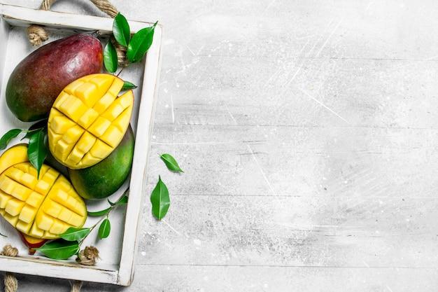 Frische reife mangos im tablett. auf rustikalem hintergrund