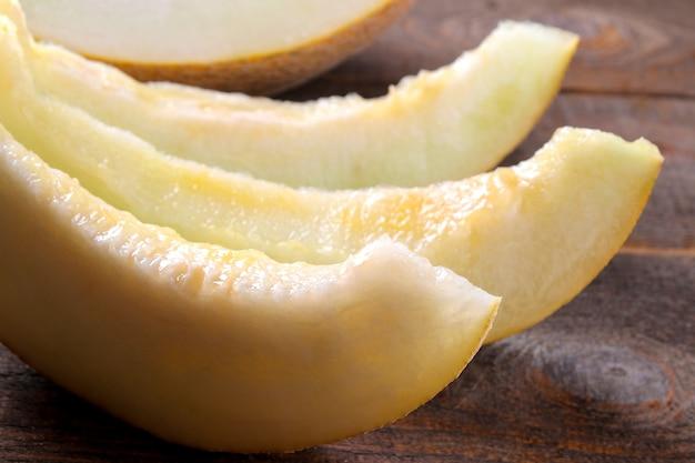 Frische reife melonenscheiben nahaufnahme auf einem braunen holztisch