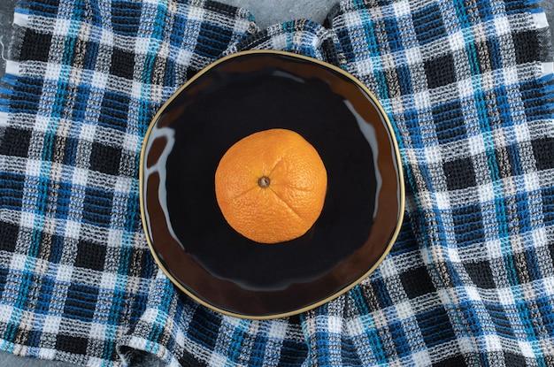 Frische reife orange auf schwarzem teller.