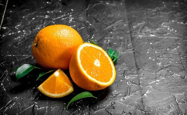 Frische reife orangen mit blättern. auf schwarzem rustikalem hintergrund