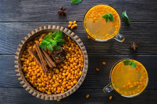 Frische reife organische sanddornbeeren in der holzschale mit zimtstangen, anissternen und minze auf dunklem tisch. zutaten für vitamingesundes getränk