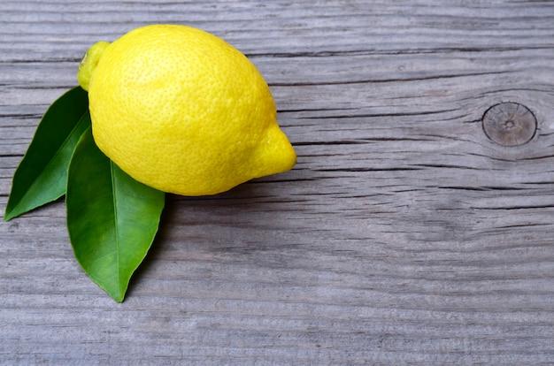 Frische reife organische zitrone auf altem hölzernen hintergrund. zitronenfrucht. gesundes essen, diät oder aromatherapie-konzept.