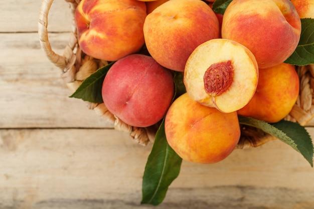 Frische reife pfirsiche in einem weidenkorb auf einem holztisch, eine scheibe saftigen pfirsichs mit einem stein. draufsicht, freier speicherplatz.