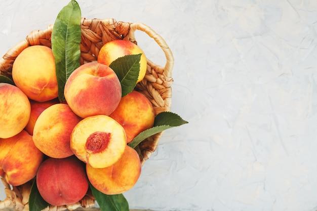 Frische reife pfirsiche in einem weidenkorb