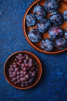 Frische reife pflaumenfrüchte in brauner hölzerner platte und traubenbeeren in der schüssel auf blauem abstraktem hintergrund, draufsicht