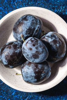 Frische reife pflaumenfrüchte in der weißen holzschale auf blauem abstraktem hintergrund, draufsicht