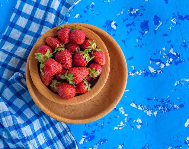 Frische reife rote erdbeere in einer braunen hölzernen ronde