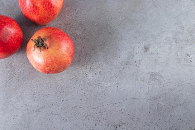Frische reife rote granatäpfel auf steinhintergrund gelegt.