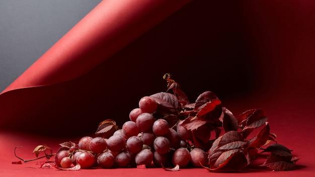 Frische reife rote trauben mit blättern auf rotem grund