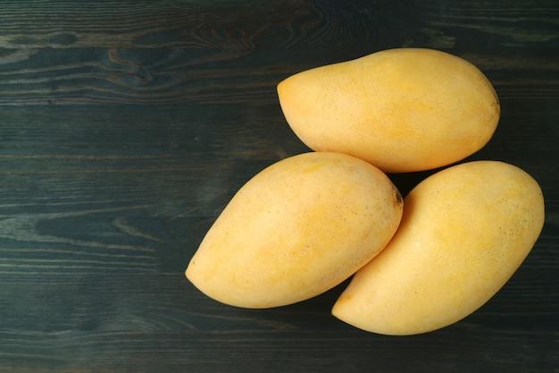 Frische reife thailändische nam dok mai mangos auf dunklem holz