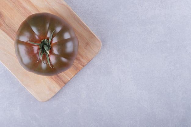 Frische reife tomate auf holzbrett.