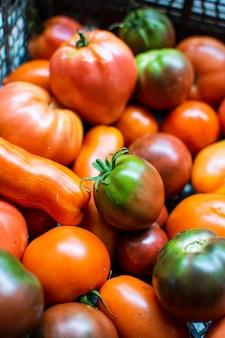 Frische reife tomaten in einer schwarzen plastikbox