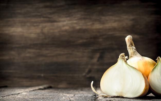 Frische reife zwiebeln. auf einem hölzernen hintergrund.