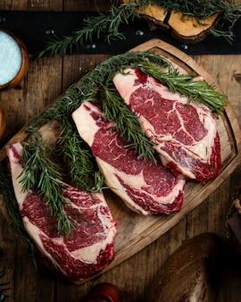 Frische rib-eye-steaks auf holzbrett