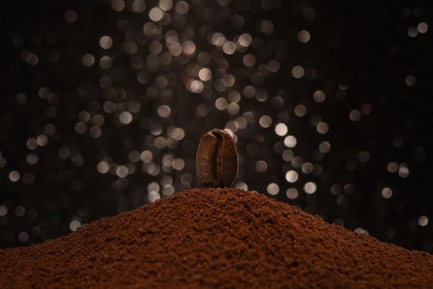 Frische röstkaffeebohne steht auf einer handvoll gemahlenem kaffee auf einem schwarzweiss-bokeh hintergrund