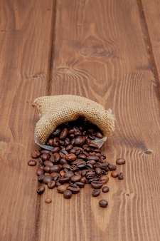 Frische röstkaffeebohnen, die den sack auf der holzoberfläche herausfallen. brown-kaffeebohnen auf dem tisch zerstreut von der tasche