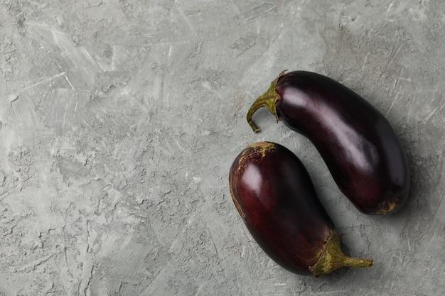 Frische rohe auberginen auf grau, platz für text
