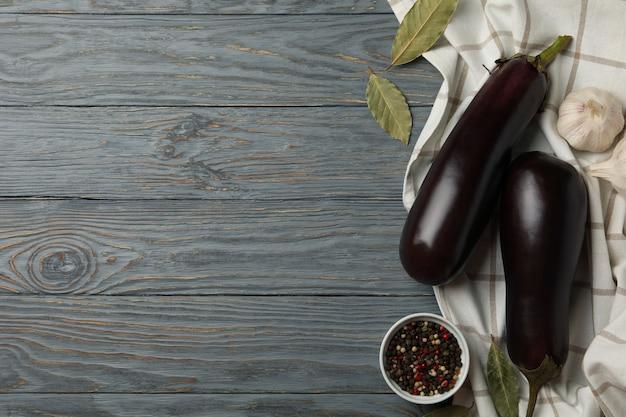 Frische rohe auberginen und gewürze auf holz