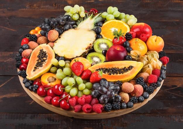 Frische rohe bio-sommerbeeren und exotische früchte im runden großen tablett auf dunklem holzküchenhintergrund. papaya, trauben, nektarine, orange, himbeere, kiwi, erdbeere, litschis, kirsche. ansicht von oben