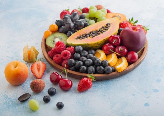 Frische rohe bio-sommerbeeren und exotische früchte in runder holzplatte