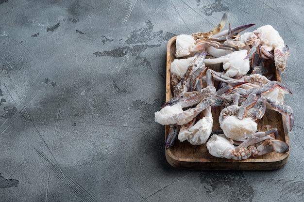 Frische rohe blumenkrabbe oder gefrorene teile der blauen krabbe gesetzt, auf holztablett, auf grauem tisch