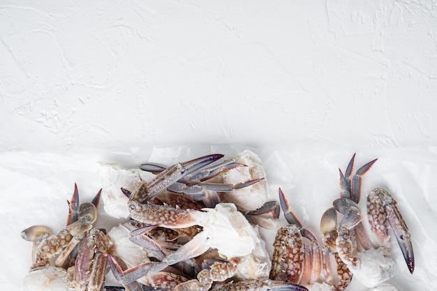 Frische rohe blumenkrabben oder blaue krabben gefrorene teile, auf weiß