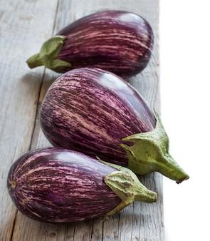 Frische rohe gestreifte auberginen auf einem alten holztisch