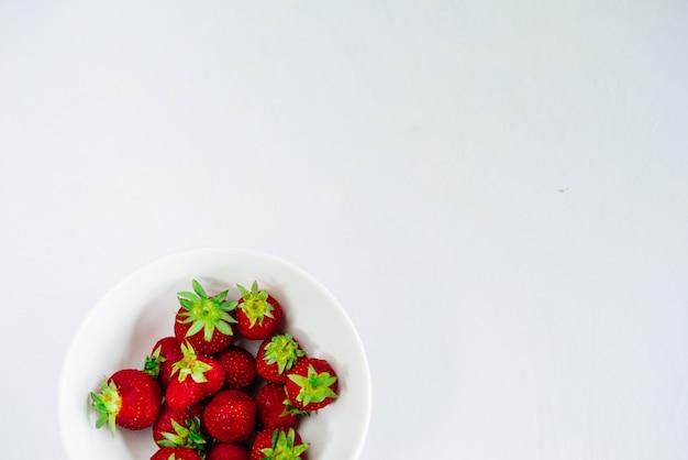 Frische rohe gesunde ernährung erdbeeren in der platte, isoliert auf weiß, ansicht oben, flatlay-nahaufnahme, exemplar für text, rahmen
