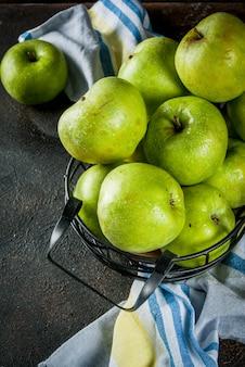 Frische rohe grüne äpfel des biohofs im schwarzen metallkorb, dunkles rostiges, copyspace