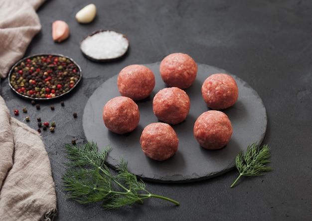 Frische rohe hackfleischbällchen auf rundem brett mit pfeffer, salz und knoblauch auf schwarzer oberfläche mit rosmarin und petersilie.