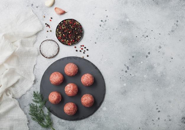 Frische rohe hackfleischbällchen auf rundem steinbrett mit pfeffer, salz und knoblauch auf heller tischoberfläche mit dill und handtuch. platz für text