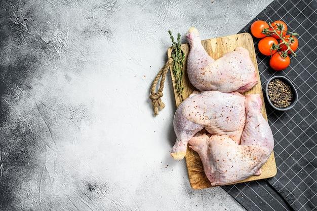 Frische rohe hähnchenschenkel, beine auf einem schneidebrett mit gewürzen, kochen. grauer hintergrund